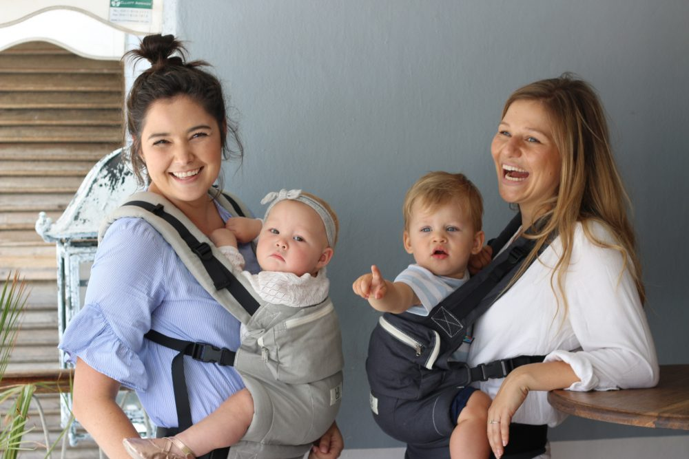 Two women laughing with babies strapped to their chest
