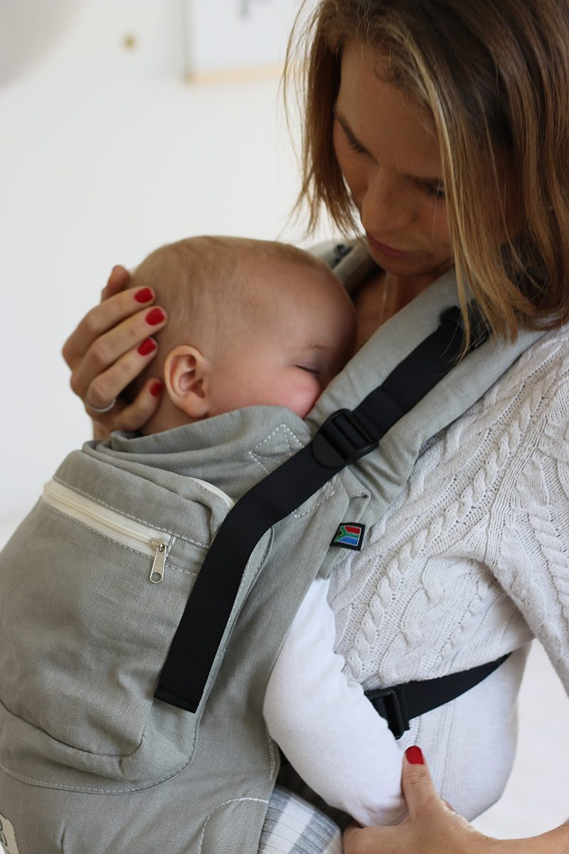 close up of baby in carrier strapped to mother