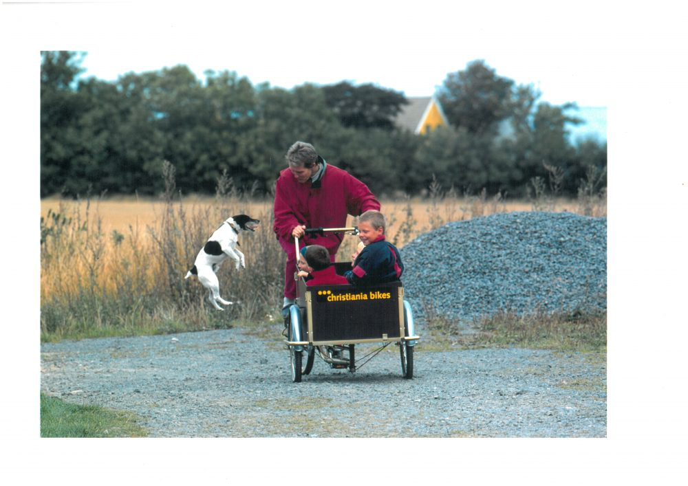 family using cargo bike with dog