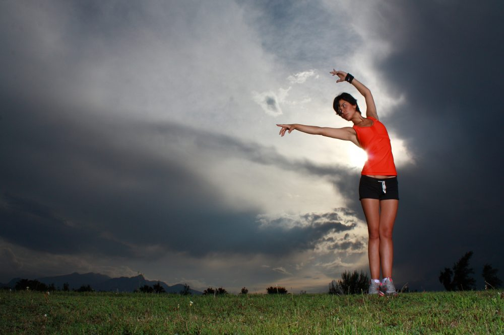 Woman doing yoga with backdrop of thunderstorm