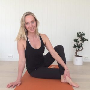 Blonde woman in black sports outfit sitting on yoga matt