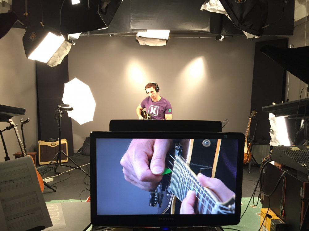 Man with guitar recording online guitar lessons