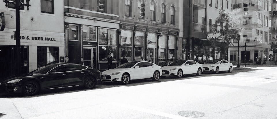 four Teslas parked in the street